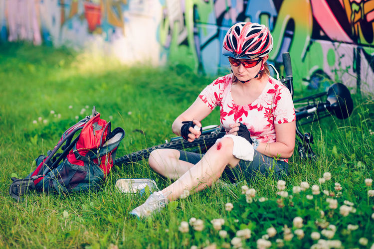 Injured Female Cyclist Applying Medicine On Wound While Sitting At Park