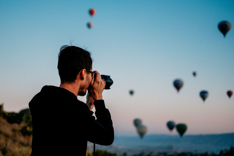Man photographing with balloons against sky