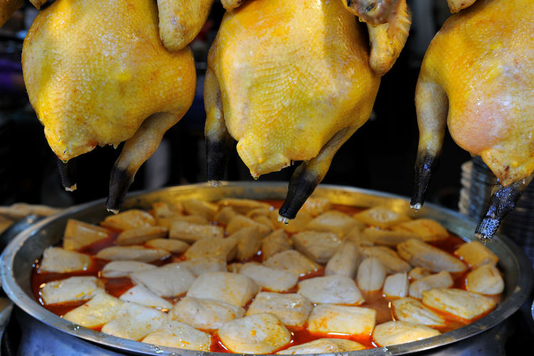 Close-up of chicken meat and food in container for sale at street market