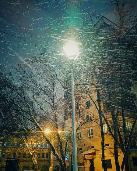 Low angle view of illuminated street lights at night