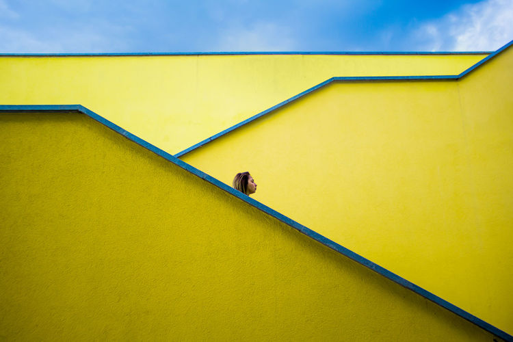 Low angle view of woman against yellow wall and sky