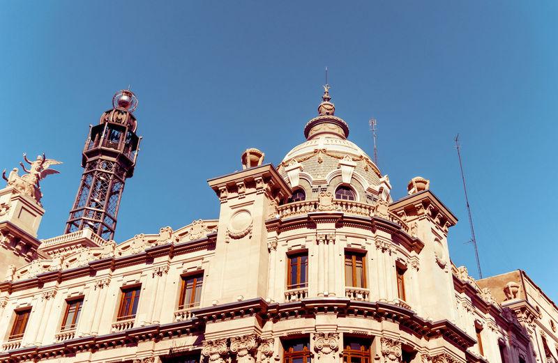 Low angle view of edificio de correos against blue sky