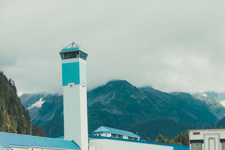 Lighthouse amidst buildings and mountains against sky