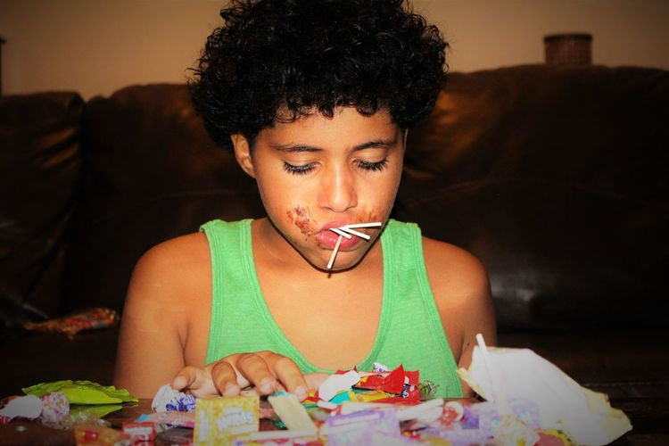 Boy with curly hair eating candies at home