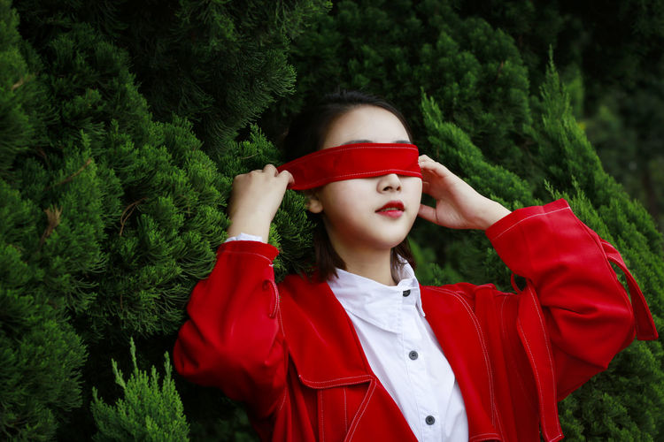 Young Woman Covering Eyes With Red Strap Against Plants