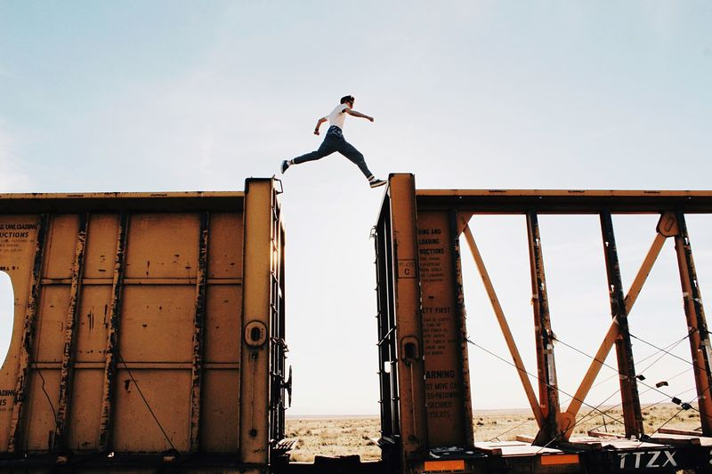 Low angle view of man jumping over metal structure against sky