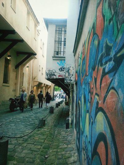 Juxtaposition d'identités urbaines: sol pavé, habitations soutenues par des poutres et graffitis