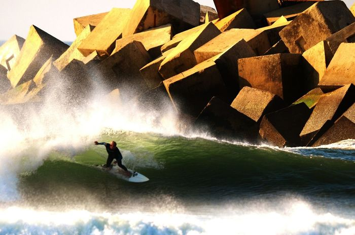 Surfer takes left wave near of espigon, in North of Spain, San Xuan Beach Asturias.