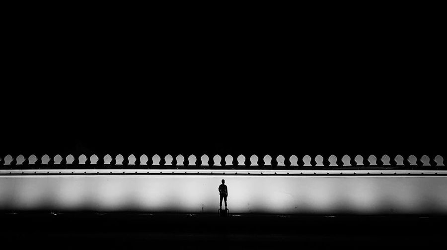 Silhouette man standing by illuminated bridge against clear sky at night