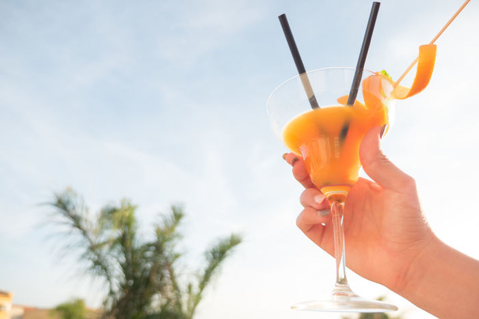 Adult Adults Only Alcohol Cocktail Drink Drinking Drinking Glass Drinking Straw Human Body Part Men One Man Only One Person Only Men Orange Juice  Outdoors People Refreshment Relaxation Sky SLICE Summer Tropical Climate Tropical Drink Vacations Young Adult