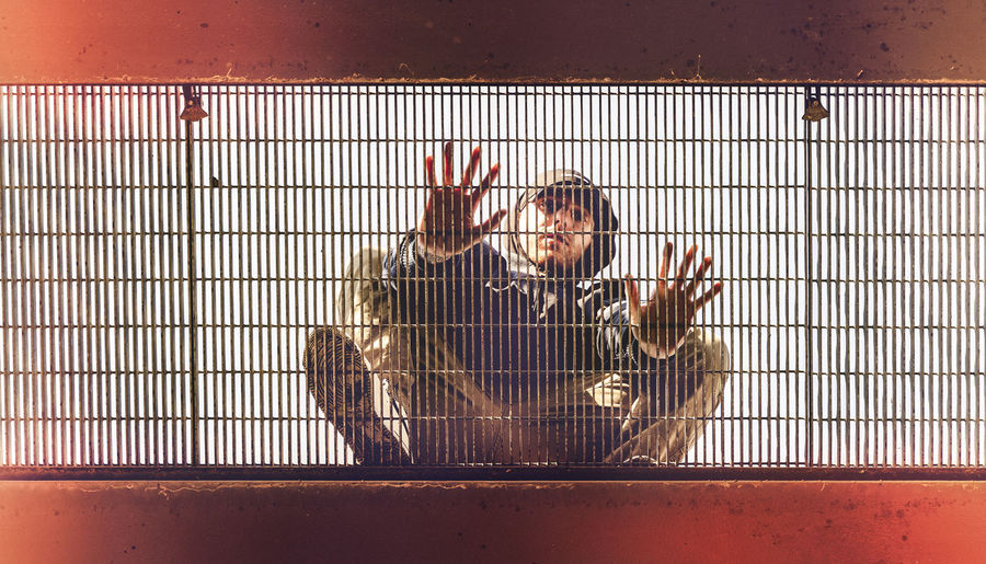 Portrait of man sitting over cage against sky