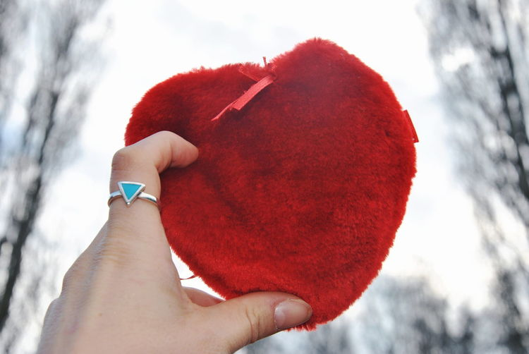 Close-up of woman holding red heart shape in winter