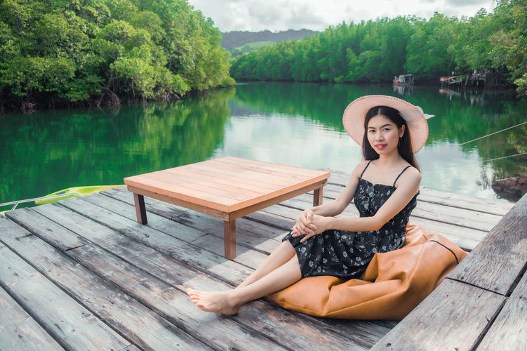 Portrait of woman sitting on wood against lake