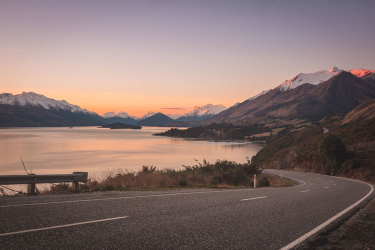 Road Leading Towards Mountains At Sunset