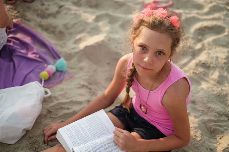 High Angle Portrait Of Girl Reading Book While Sitting At Beach