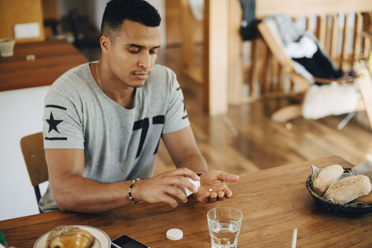 Young man looking away while sitting on table