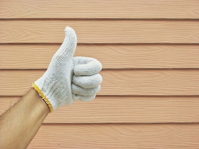 Man's hand in cotton fabric glove showing thumb up gesture with blurred orange painted shera wood wall background after completely wall painted Pattern Lifestyle Outside Exterior Work Vintage Tone Thump Up Gesture Signal Man Painter Completely Decor Shera Wood Wall Cotton Fabric Glove Human Hand Wood - Material Backgrounds Wool Close-up Knotted Wood Textured  Rough Bark Glove Wood Paneling Rugged Wooden Woven
