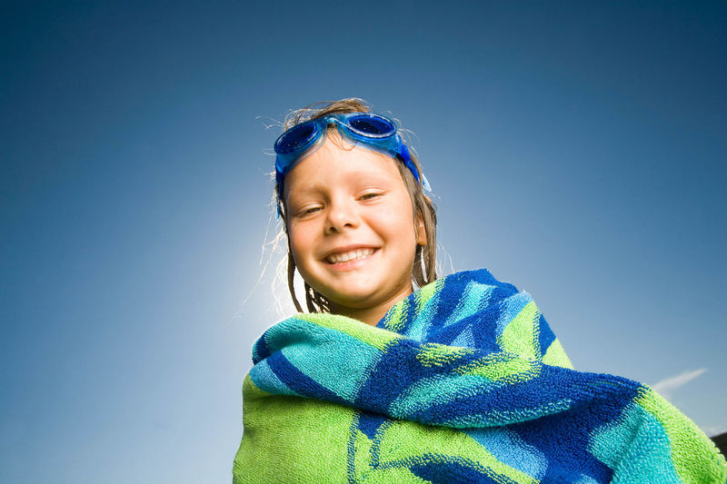 Portrait of happy girl covered with towel against blue sky