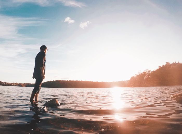 Young man standing in lake against sky during sunset