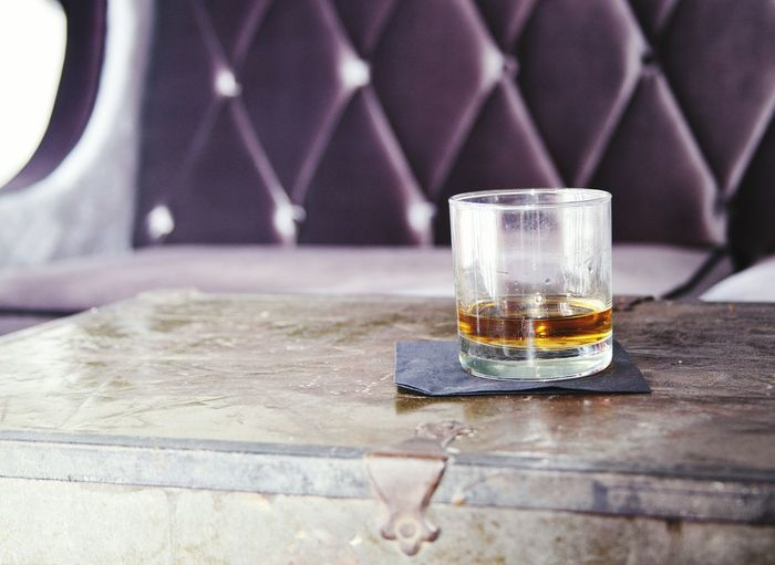 Bourbon whiskey on table by sofa
