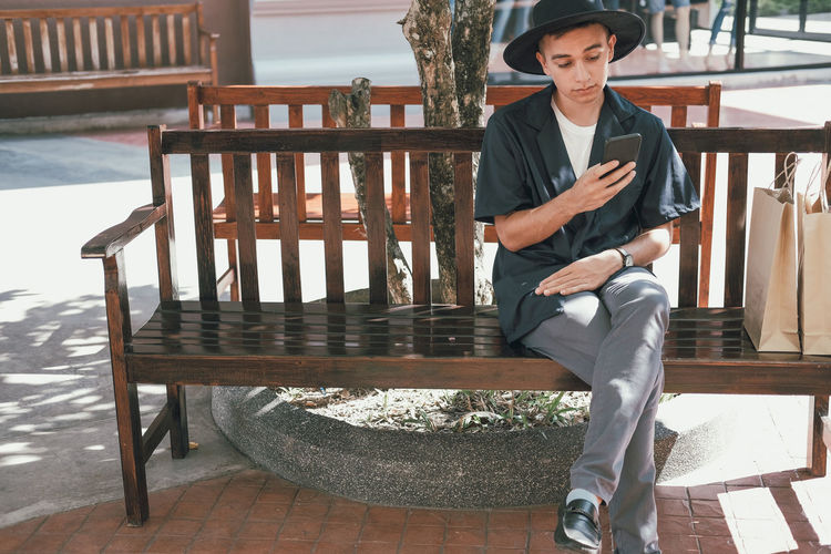 Man using mobile phone while sitting with shopping bags on bench outside store