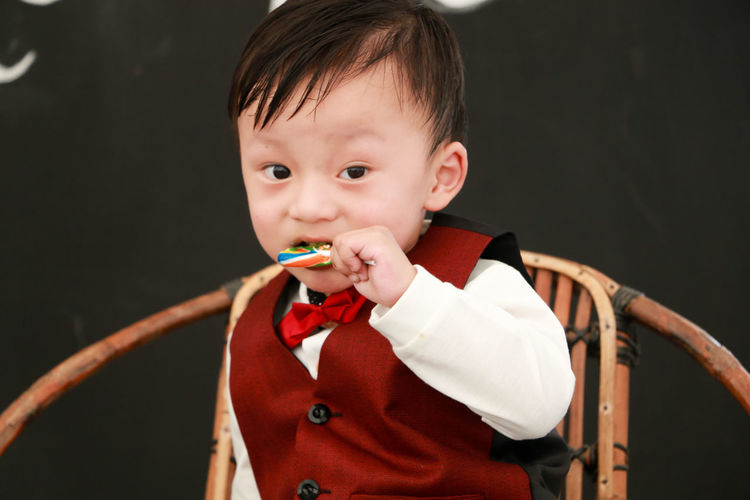 Portrait Of Cute Boy Eating Candy