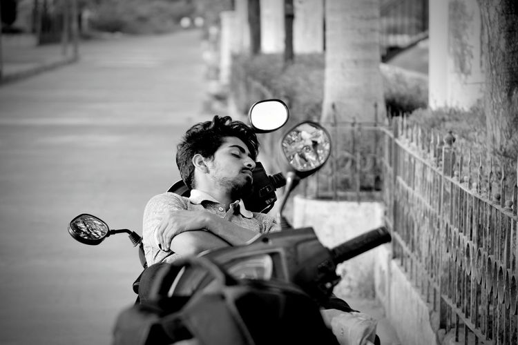 High Angle View Of Young Man Sleeping On Motor Scooter