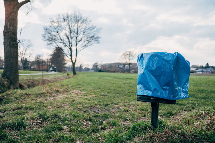 Garbage can with blue plastic bag in front in front of trees