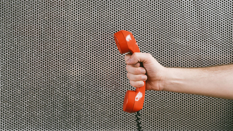 Red phone against metallic wall background with holding hand concept for customer support line or important call Business Calling Communicate Discussing Emergency Listening Red SUPPORT Service Social Wall Call Communication Contact Holding Human Hand Metal Mettalic Old Phone Speaking Talk Telecom Telecommunications Telephone Vintage