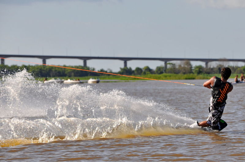Man surfing in river against sky