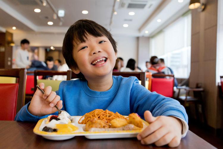 Portrait of boy eating food in restaurant