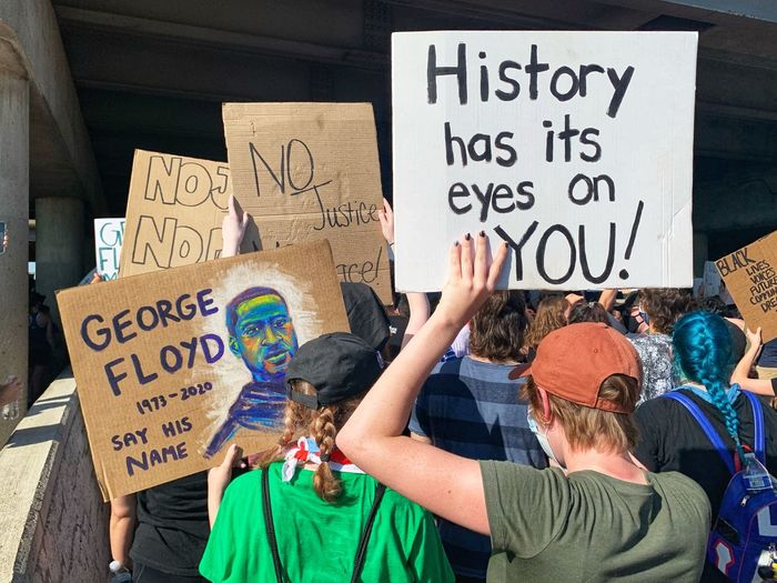 Blm protestors holding george floyd sign