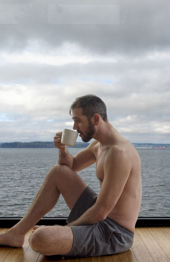 Side View Of Shirtless Man Having Coffee While Sitting By Window Against Sea