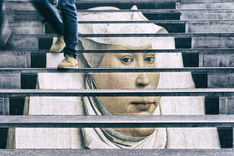 Medieval painted portrait of a woman as advertisement for Berlin museums on stairs of Potsdamer Platz Station in Berlin, Germany Advertisement Berlin Close-up Color Image Day Germany Horizontal Human Body Part Human Leg Medieval No People One Person Outdoors People Photography Portrait Of A Woman Staircase