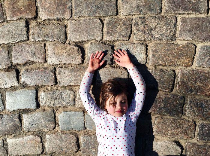 Girl Lying On Cobblestone
