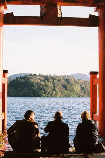 Rear view of people on lake against clear sky