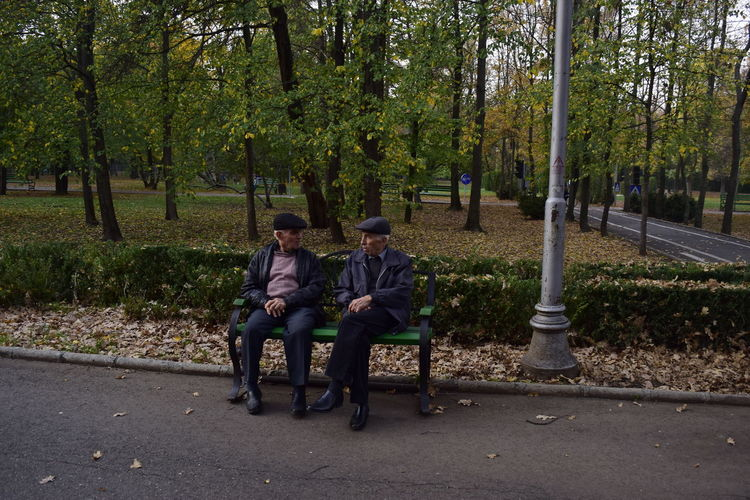 Adult Day Full Length Men Nature Outdoors People Real People Sitting Togetherness Tranquil Scene Outdoors Two People