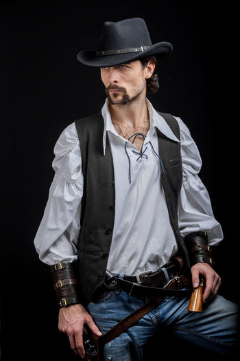 Handsome young man. This is an American cowboy. A vow to a white shirt, brown waistcoat and blue jeans. Black shoes on the feet. Carries a shtyapa, on a belt two pistols. The hair is of medium length; on the face is a beard and mustache. Authentic photo. Culture of America. Cowboy Wild West America American Gun National Authentic Moments Lifestyles Lifestyle One Person Candid Authentic Hat Black Background Front View Clothing Three Quarter Length Men Beard Standing Casual Clothing Adult Males  Weapon Arts Culture And Entertainment