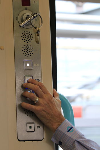 Close-up of man pressing button in train