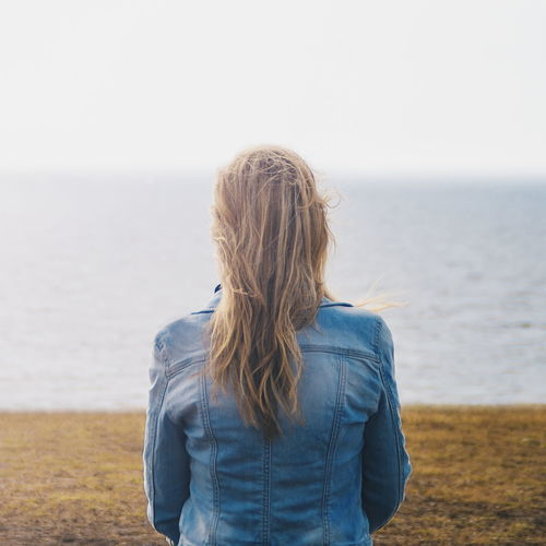 Rear view of woman sitting at beach against clear sky