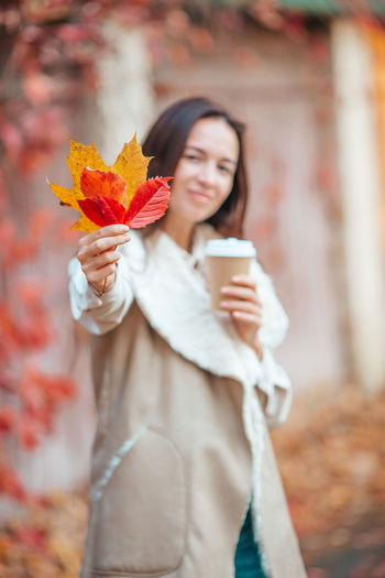 Young woman using mobile phone while standing on sidewalk during autumn