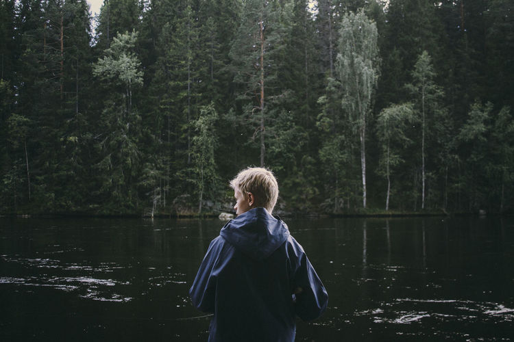 Rear view of boy looking away while standing by lake against trees