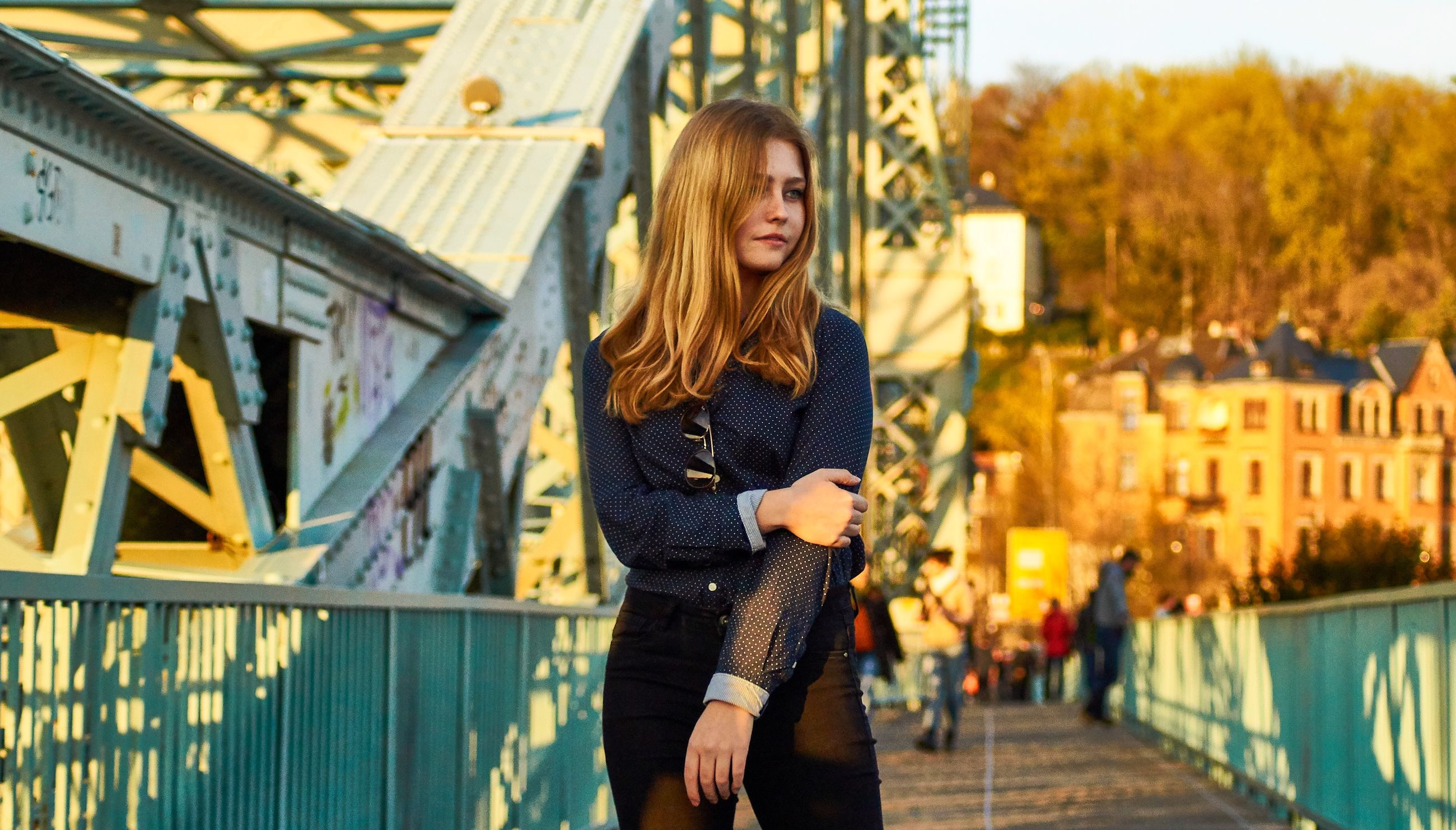 one person, young adult, young women, real people, long hair, architecture, leisure activity, casual clothing, lifestyles, hair, hairstyle, three quarter length, focus on foreground, standing, beauty, beautiful woman, built structure, railing, outdoors, change