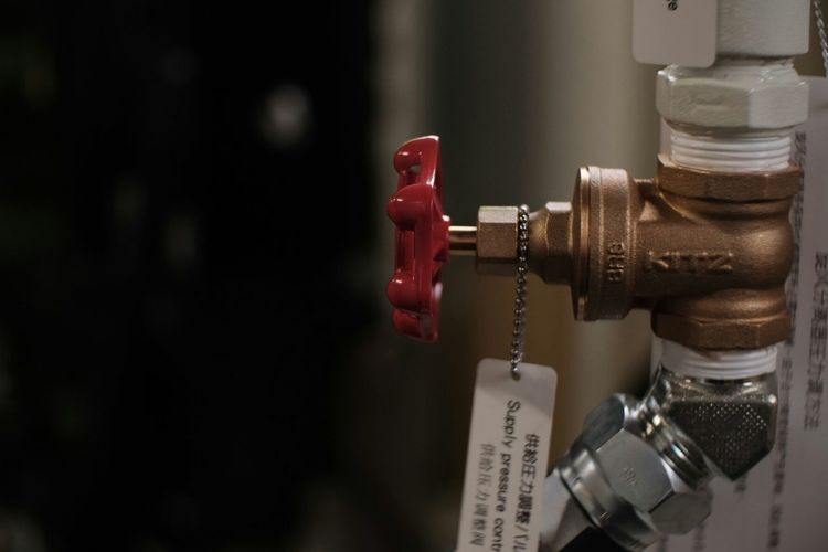 Close-up side view of tap against blurred background
