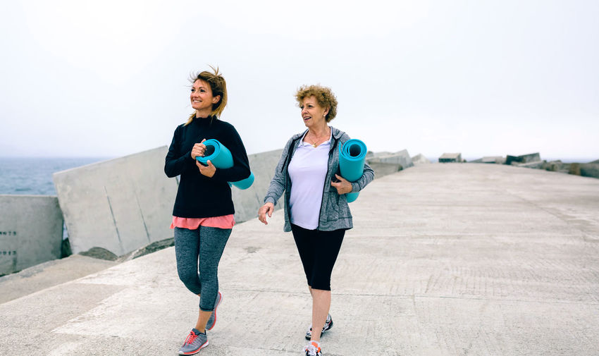 Full Length Of Women With Exercise Mats By Sea On Walkway