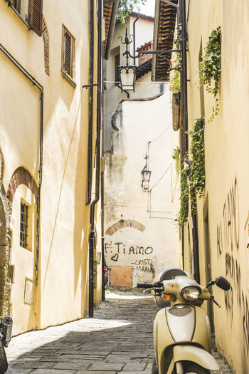 """Picturesque yellow Tuscan street with a yellow scooter and a writing on the wall """"Ti amo"""" Building Exterior Street Day No People Window Outdoors Sunlight City Architecture Built Structure Building Moto Motorcycle Tuscany Toscany Street Italy Italy❤️ Yellow Yellow Street Lamp Picturesque Scenery Scooter"""