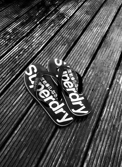 Flip-flops Text Writing Angled View Backgrounds barefoot Barefoot Lifestyle Big Feet Blackandwhite Day Decking Decking Wood Flip-flop Flipflops Footwear No People Outdoor Outdoors Personal Accessory Randomshot Shoe Still Life Summer Textured  Wood - Material Wood Grain