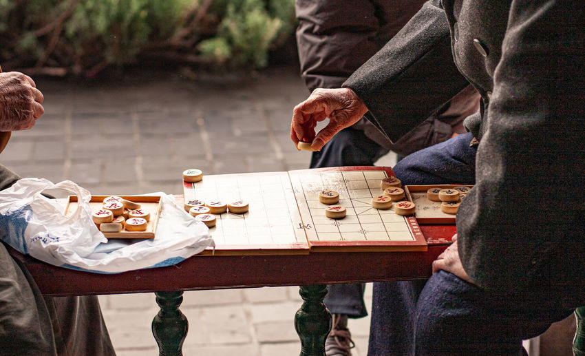 People sitting on table playing a traditional board game with wooden counters.