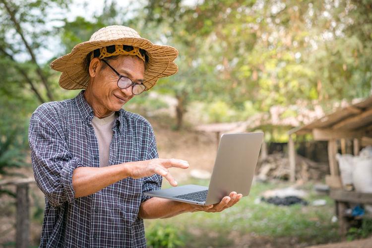 Senior man using laptop in farm