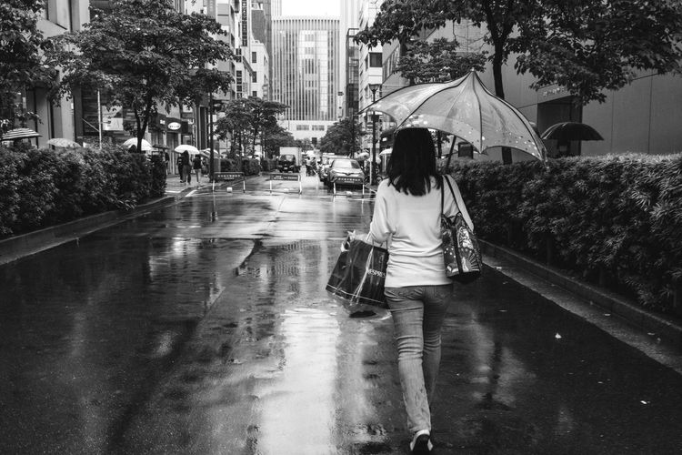 A woman out walking with a unique umbrella on a rainy Tokyo day. Black & White Reflection Woman Architecture Black And White Blackandwhite Blackandwhite Photography Building Exterior City Lifestyles People Rain Rainy Season Real People Rear View Street Street Photography Streetphoto_bw Streetphotography Umbrella Urban Water Wet Women